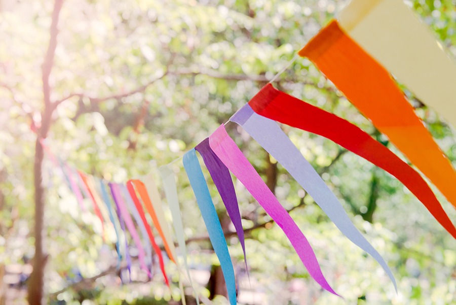 Close up of a colorful party banner tied between trees in a park at an open air celebration event
